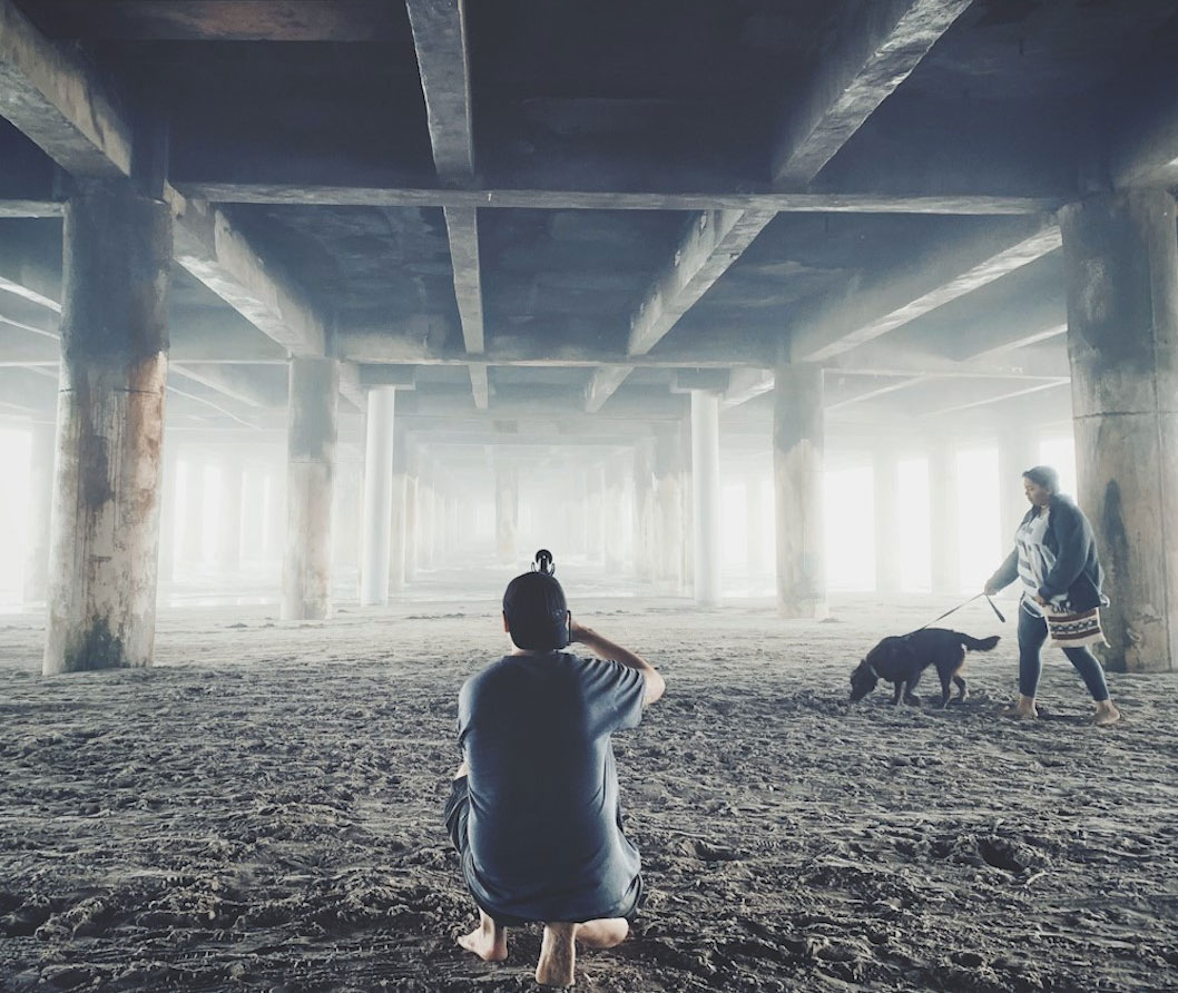 A photographer kneels down in the sand while taking a photo of a woman walking her dog beneath a pier by the ocean.